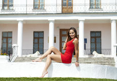 Beautiful young girl in short red dress sitting on the white sto Royalty Free Stock Photo
