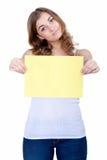 Beautiful young girl shows a blank sheet of yellow Stock Photo