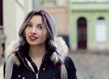 Beautiful young girl with silver gray braid hair, red lips wearing black down jacket walking on the street in warm winter Royalty Free Stock Photo