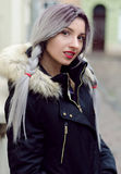 Beautiful young girl with silver gray braid hair, red lips wearing black down jacket walking on the street in warm winter Royalty Free Stock Photography