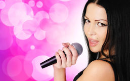 Beautiful young girl singing in microphone. On abstract background Royalty Free Stock Image