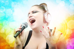 Beautiful young girl singing in microphone. On color abstract background Royalty Free Stock Photos