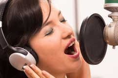 Beautiful young girl singing in music studio. Beautiful young brunette girl singing in music studio Royalty Free Stock Images
