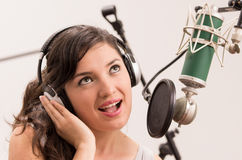 Beautiful young girl singing in music studio. Beautiful young brunette girl singing in music studio Stock Images