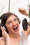 Beautiful young girl singing in music studio Royalty Free Stock Photos