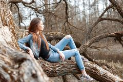 Beautiful young girl sits and dreaming on a tree branch. Stock Photography