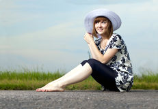 Beautiful young girl sits in a hat Royalty Free Stock Photography