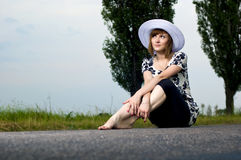 Beautiful young girl sits in a hat Stock Photo