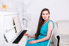 Beautiful young girl sits near the white piano and stares Royalty Free Stock Images