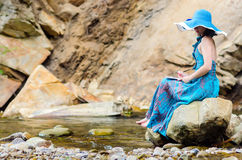 Beautiful young girl sits on a rock in the river Royalty Free Stock Photo