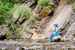 Beautiful young girl sits on a rock in the river Royalty Free Stock Image