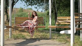 Beautiful young girl sits in summer park on a bench stock footage