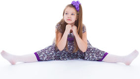 A beautiful young girl sits on a twine. Stock Image