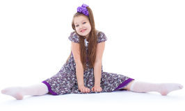A beautiful young girl sits on a twine. Stock Images
