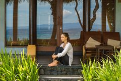 Beautiful young girl sits on the veranda the bungalow near the ocean beach in Bali island Indonesia