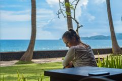 Beautiful young girl sits and waiting for a phone call on the veranda the bungalow on the ocean beach in Bali island Indonesia royalty free stock image