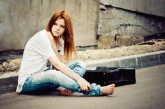 Beautiful young girl sitting on asphalt Stock Images