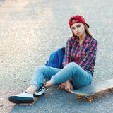 Beautiful young girl sitting on the asphalt with a skateboard. O Stock Photography