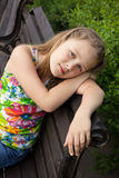 Beautiful young girl is sitting on the bench Stock Photos