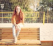 Beautiful young girl sitting on a bench on a warm summer day Stock Image