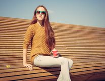 Beautiful young girl sitting on a bench on a warm summer day whis cuo of coffee Royalty Free Stock Image