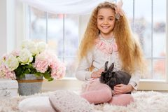 Beautiful young girl sitting on carpet and playing with cute bunny. Stock Image