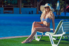 Beautiful young girl is sitting on the chaise-longue with pleasure near a swimming pool. She is wearing beautiful royalty free stock photography