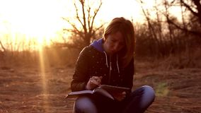 Beautiful young girl, sitting on a fallen autumn leaves in a park, reading tablet computer to take notes in a notebook stock video footage