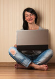 Beautiful young girl  sitting on the floor with a laptop Royalty Free Stock Photos
