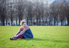 Beautiful young girl sitting on the grass Stock Photos
