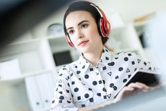 Beautiful young girl sitting in headphones at desk in office. Photo with depth of field, focus on girl. Beautiful young girl in a white blouse in a geometric stock photos