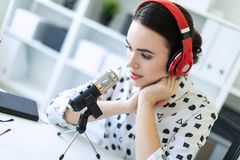 Beautiful young girl sitting in headphones and with microphone at table in office and talking. Beautiful young girl in a white blouse in a geometric pattern and Royalty Free Stock Photography