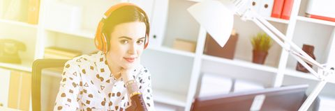 Beautiful young girl sitting in headphones and with microphone at table in office and talking. Beautiful young girl in a white blouse in a geometric pattern and stock photos