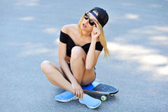 Beautiful young girl sitting on longboard Royalty Free Stock Images