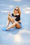 Beautiful young girl sitting on longboard Stock Image