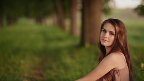 Beautiful young girl sitting near a tree, singing a song. Close-up. stock video