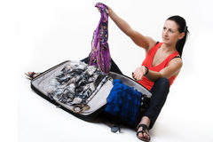 Young woman preparing her baggage before travel. Beautiful young girl sitting next to her suitcase and preparing clothes for her trip. She is choosing which Stock Photos