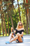 Beautiful young girl sitting over a skateboard Stock Images