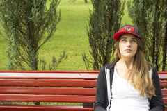 Beautiful young girl sitting on a park bench. Girl in a cap with the inscription. She looks ahead up. Behind girl green lawn and trees Royalty Free Stock Photos
