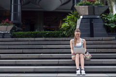 Beautiful young girl sitting on the stairs with the laptop. The girl looks at the screen. Royalty Free Stock Image