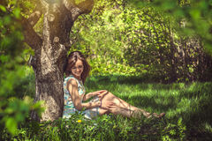 Beautiful young girl sitting under a big oak outdoors Royalty Free Stock Photo