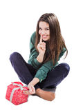 Beautiful young girl sitting on a white background holding a box with a gift. Smiles. Stock Images