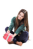 Beautiful young girl sitting on a white background holding a box with a gift. Smiles. Beautiful young girl sitting on a white background holding a box with a Stock Photography