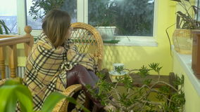 Beautiful young girl sitting in a Wicker Chair and is wrapped in a blanket and falls asleep at home stock video footage