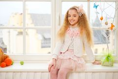 Beautiful young girl sitting on a windowsill at cozy home atmosphere. Stock Image