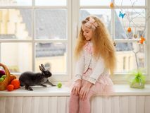 Beautiful young girl sitting on a windowsill and playing with Easter bunny. Royalty Free Stock Images