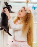 Beautiful young girl sitting on a windowsill and playing with Easter bunny. Royalty Free Stock Photography