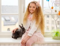 Beautiful young girl sitting on a windowsill and playing with Easter bunny. Stock Images