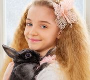 Beautiful young girl sitting on a windowsill and playing with Easter bunny. Royalty Free Stock Image