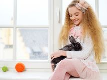 Beautiful young girl sitting on a windowsill and playing with Easter bunny. Stock Image